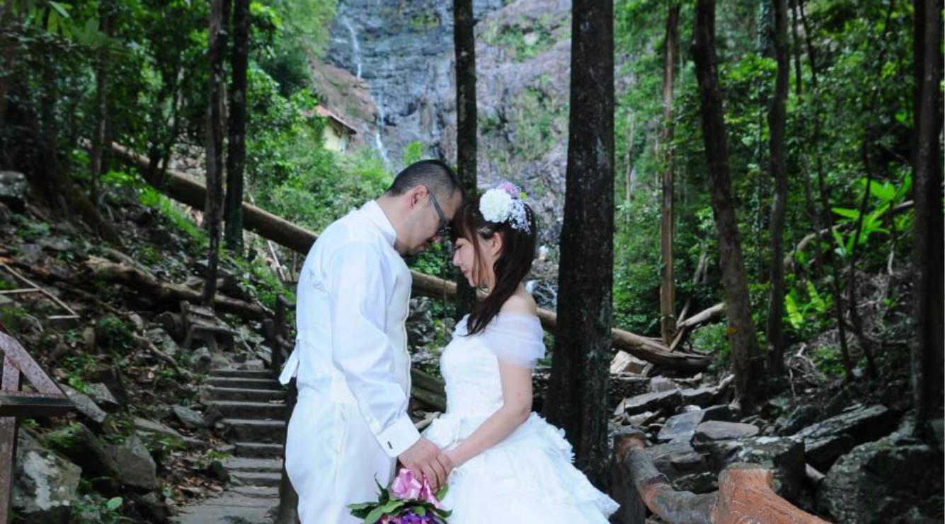 テムルン滝近くの遊歩道でポーズを取るカップル