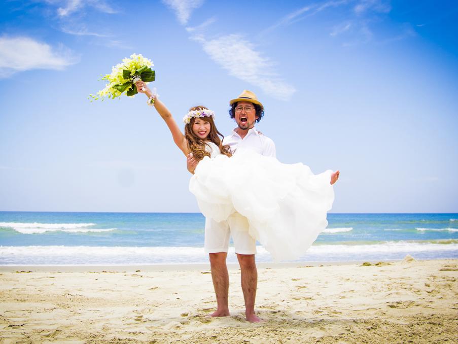 美しい浜辺で新婦をお姫様抱っこする新郎